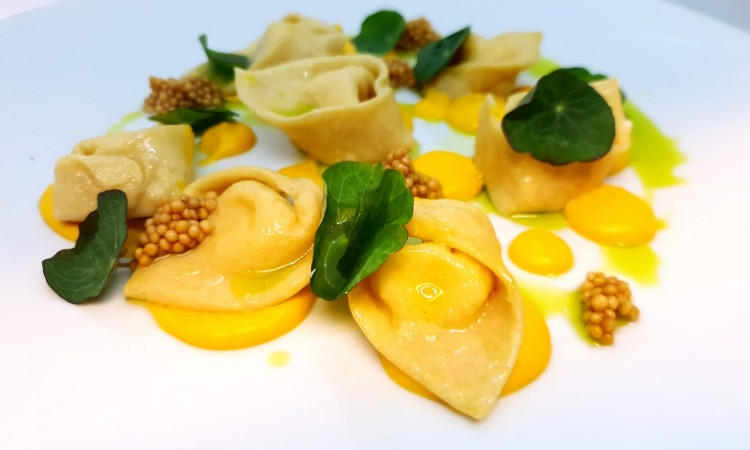 Goat cheese and roasted garlic tortelloni with butternut squash pure and pickled mustard seeds-min