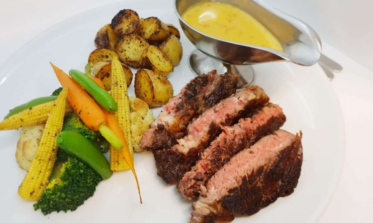 Rib eye steak with garlic roasted potatoes, Seasonal vegetables and green peppercorn sauce-min
